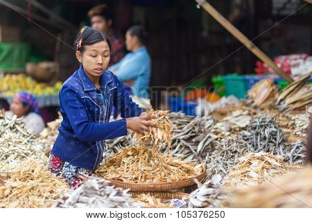 MANDALAY,MYANMAR,JANUARY 17, 2015: A  woman is selling dry fish in the central street market of Zegyo, in Mandalay, Myanmar (Burma).