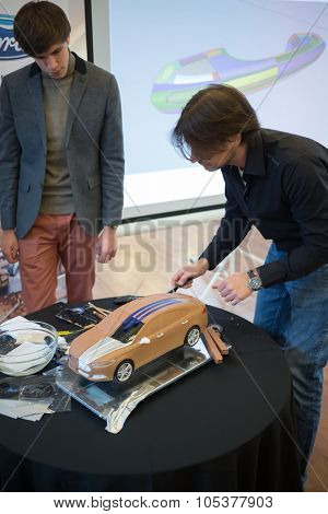 RUSSIA, MOSCOW -?? 4 DEC, 2014: Man makes line with a knife on the roof of the car model at the press event for Ford in SREDA loft.