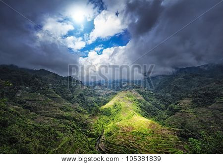 Ray of sun light through clouds under rice terraces in Philippines highlands