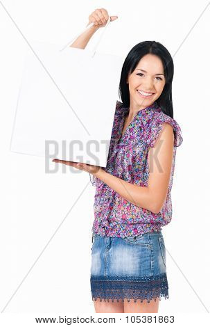 Portrait of young happy smiling woman showing white shopping bag, isolated over white background