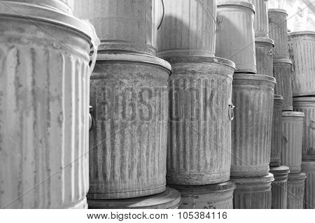 Old galvanized steel metal trash cans in black and white