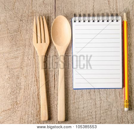 Open Cookbook,pencil And Kitchenware On Wooden Background