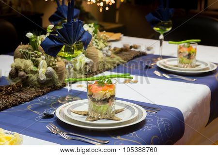 Decorated Christmas dinner table with seafood verrine as a starter