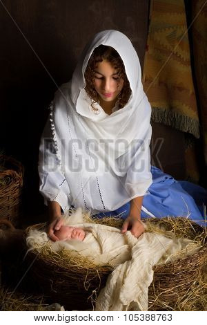 Teenager girl playing the role of the Virgin Mary with a doll in a live Christmas nativity scene (the baby is a doll)
