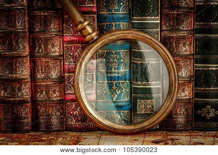 Ancient old books and magnifying glass