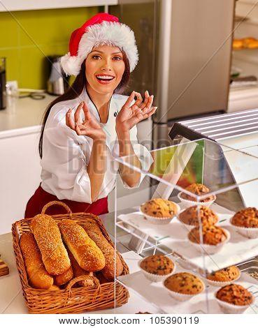 Girl wearing  santa hat seller sells fresh bread in store.