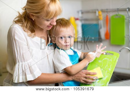 Mother And Kid Son Washing Dishes