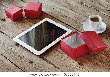 White Tablet With Open Gifts And A Cup Of Coffee