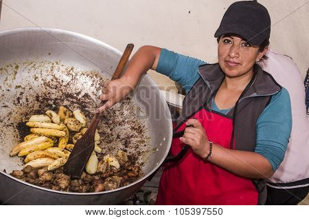 Hispanic woman showing typical Ecuadorian food preparation, pieces of pork and baby bananas being fr
