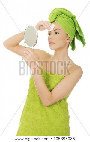 Beautiful spa woman with cotton pad and mirror.
