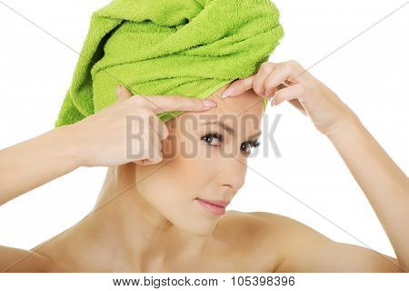 Beauty woman checking wrinkles on her forehead, closeup