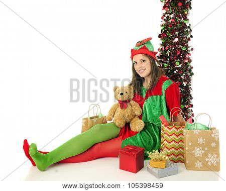 A pretty teen Christmas elf looking at the viewer as she happily relaxes among Santa's gifts.  On a white background with space on the left for your text.