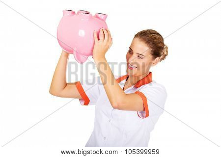 Young beautiful female doctor or nurse holding a piggybank.