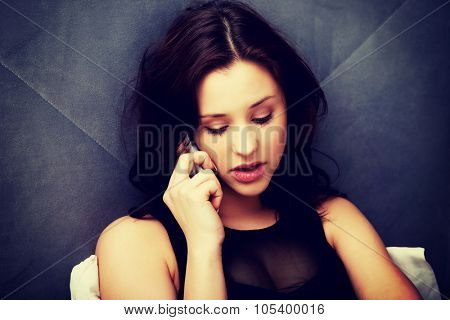 Relaxed woman talking on the phone in bedroom.