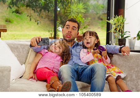 Family portrait of father and two daughters sitting together in sofa posing for selfie making funny