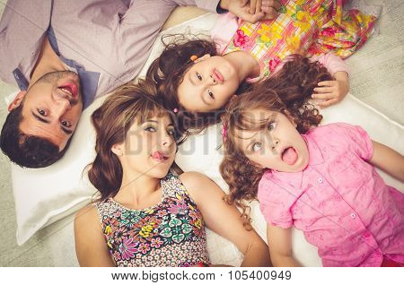 Young adorable hispanic sisters and parents lying down with heads touching, bodies spread out differ