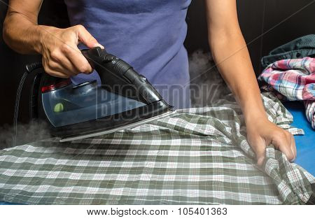 woman in a blue T-shirt ironing plaid shirt and other clothing