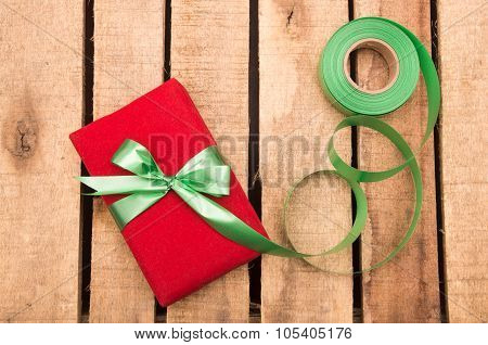 Nicely wrapped presents in red and green wrapping on wooden surface