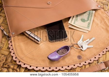 Womans purse beige color lying flat with accessories such as mobile, makeup, keys and money spread o