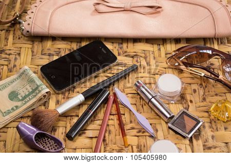 Womans purse accessories concept with phone, money and makeup spread out, closeup shot