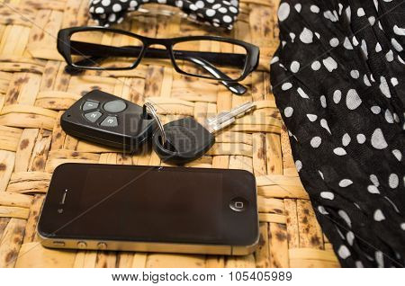 Personal belongings of typical woman, daily life concept, mobile phone, car keys, glasses and money