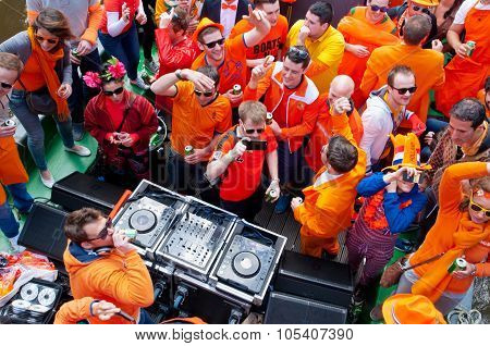 People Dressed In Orange Celebrate King's Day On A Boat.