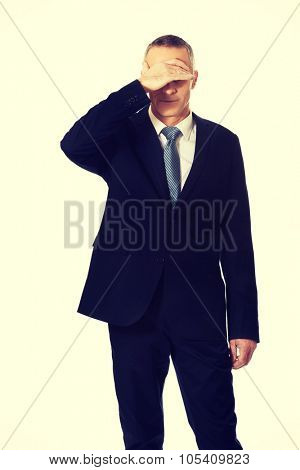 Mature embarassed businessman covering his face.