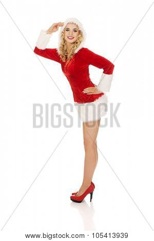 Young beautiful santa woman salutes.