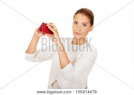 Shocked businesswoman looking into her empty wallet.