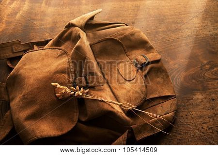Leather backpack or knapsack and strand of dried grass in warm rustic lighting.  Intentionally shot with retro feel and low key shadows.