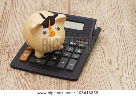 A Golden Piggy Bank With Grad Cap And Calculator On Wood Background