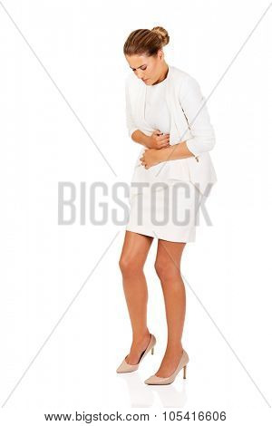 Young businesswoman suffering from stomach ache.