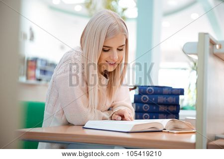 Portrait of a happy young woman reading book in university