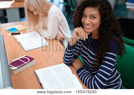 Portrait of a happy female students reading books in university