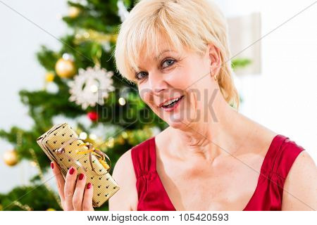 Senior woman is curious about Christmas gift