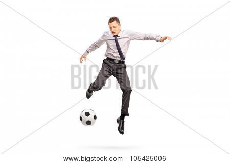 Full length portrait of a young businessperson kicking a football shot in mid-air isolated on white background