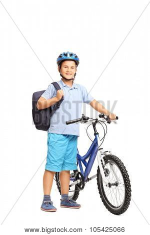 Full length portrait of a cute little schoolboy carrying a backpack and posing next to his bicycle isolated on white background