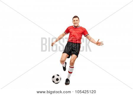 Full length portrait of a determined young football player shooting a ball and looking at the camera isolated on white background