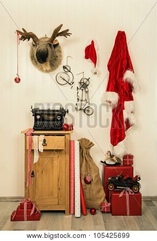 Vintage christmas decoration in red and white with santa, elk, presents and an old typewriter.