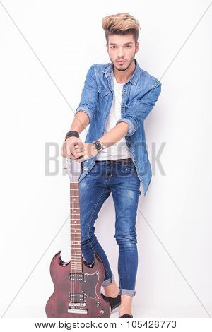 full body picture of a young guitarist holding down his electric guitar on white background
