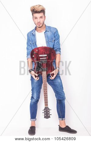 cool young guitarist showing his red electric guitar on white background