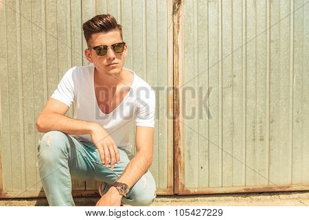 handsome skinny man pose outside sitting with hand on his knee looking away