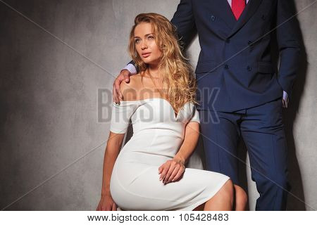 sexy woman in white dress is sitting and looks away from the camera while a gentleman is holding her by her shoulder. hot elegant couple in studio
