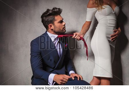 elegant man looking at his lover while she is pulling his tie and walks away in studio