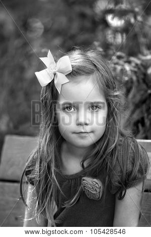 black and white portrait of little girl sitting on a bench outside