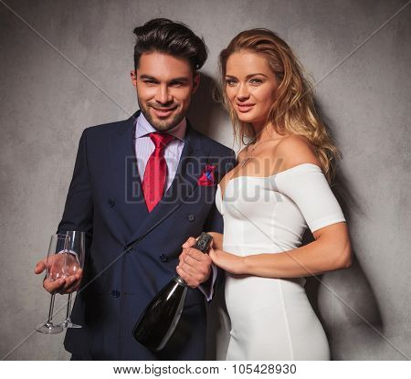 happy smiling elegant couple holding a bottle of champagne and glasses inviting you to a party