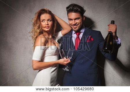 man holding a bottle of champagne saying cheers with his woman next to him. hot fashion couple ready to celebrate