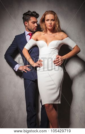 hot elegant fashion couple standing with hands on hips in studio, woman in front of her man.