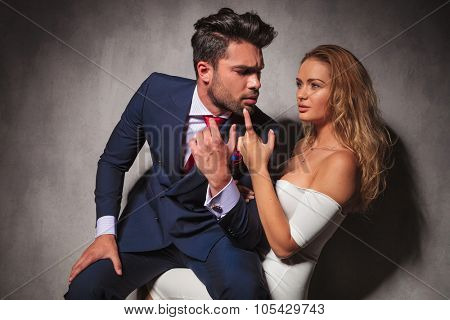 elegant man is sitting on sexy blonde woman's knees, she is holding his chin with her finger. sensual couple in studio