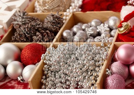 Shiny christmas ornaments in a wooden compartment.